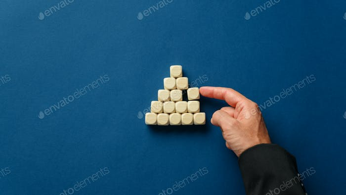 Business executive building a pyramid shape with wooden dices