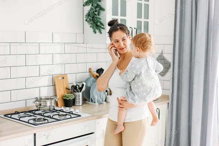 Young woman mom with baby girl on hands using mobile on kitchen