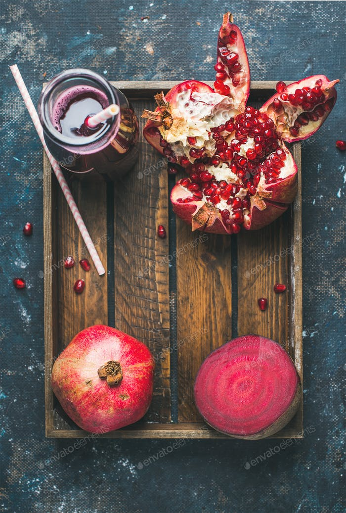 Ripe seasonal pomegranates, beetroot and freshly squeezed juice in glass