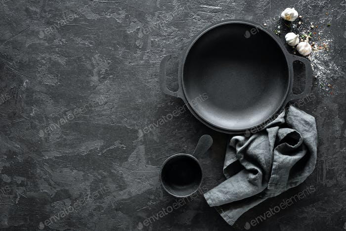 Empty cast-iron pan on dark background for restaurant menu, top view