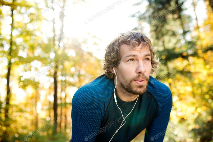 Young handsome runner with earphones outside in autumn nature