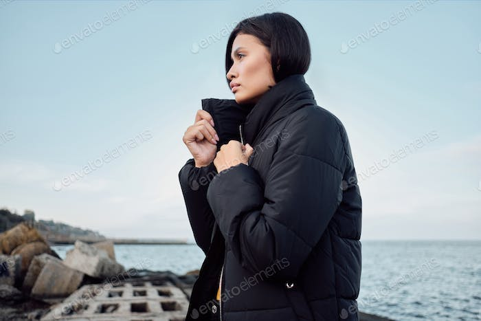 Side view of gorgeous Asian brunette girl in down jacket intently looking away on seaside