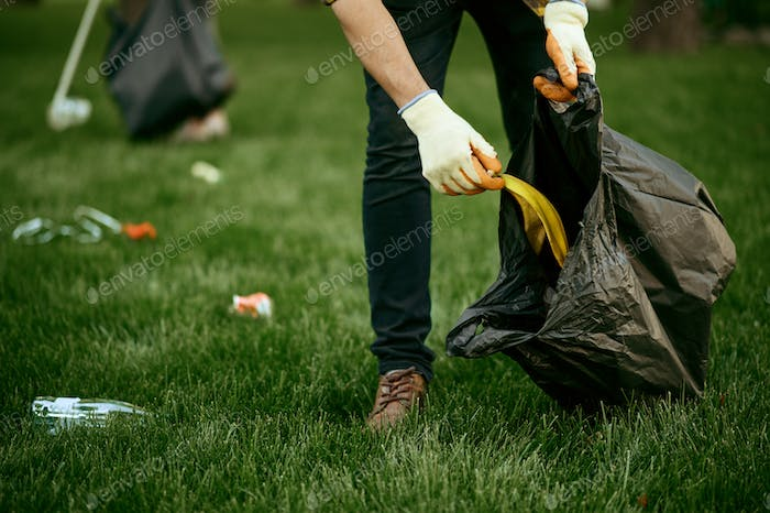 Young man collects garbage in a bag, volunteering