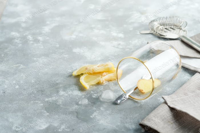 Refreshing ginger in a glass with drop water on a marble grey table