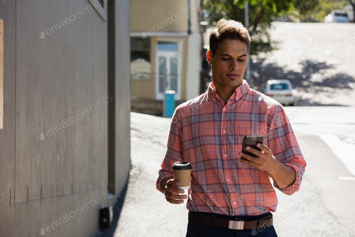 Young man using phone while walking by building