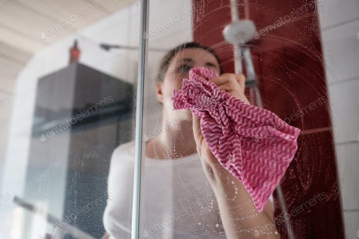 Caucasian woman cleaning shower stall in the bathroom