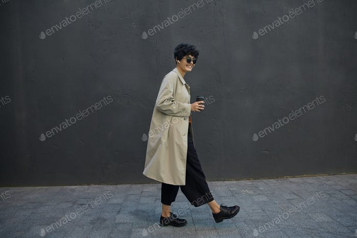Stylish dark haired hipster female with short curly hair walking in city against black urban wall