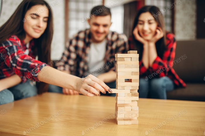 Friends plays jenga, selective focus on tower