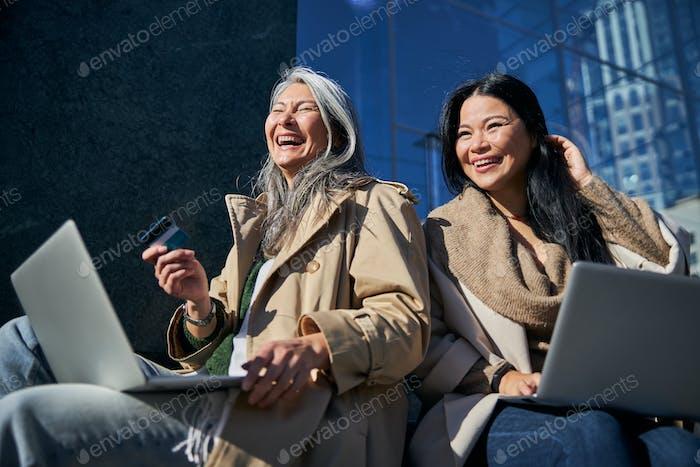 Alegres amigas usando laptops para comprar online