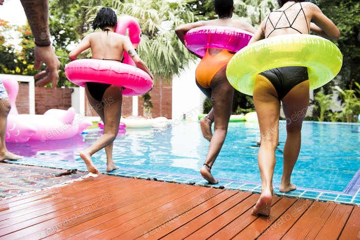 Group of diverse women jumping to the pool with inflatable tube