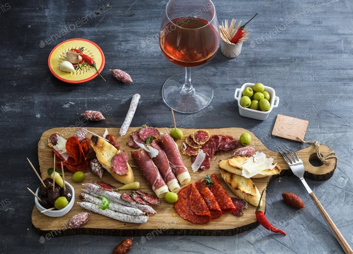 Typical spanish tapas concept. include variety slices jamon, chorizo, salami. Copyspace.