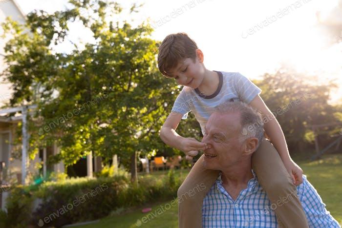 Grandfather and grandson at home in their garden
