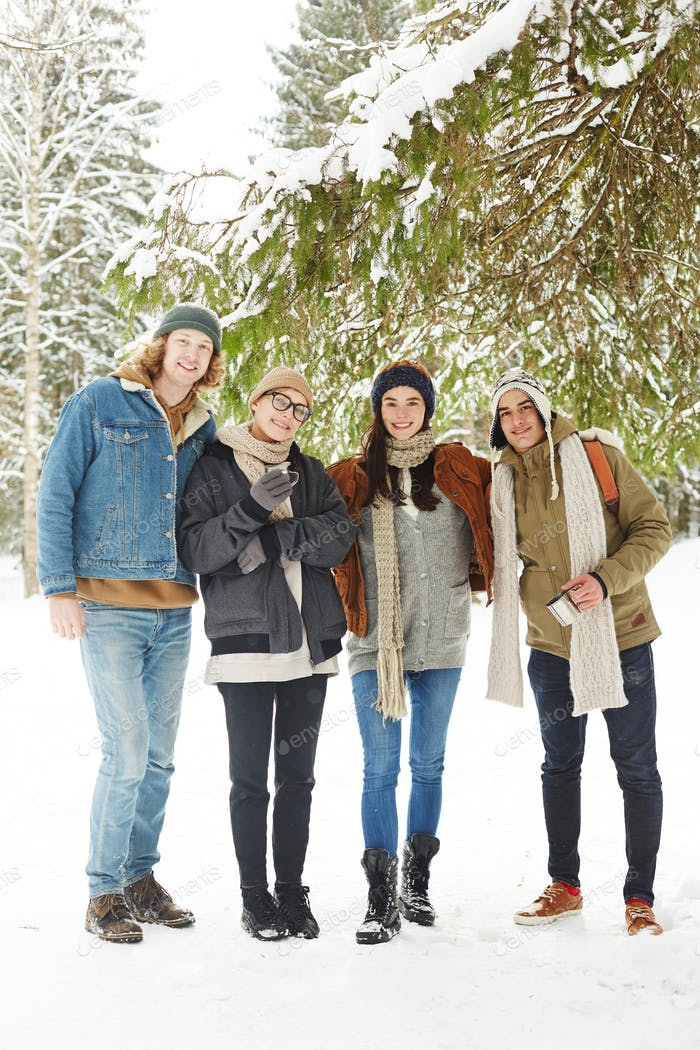 Group of Young People in Snowy Winter Forest