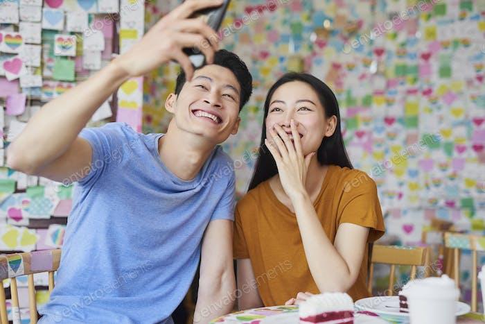 Vietnamesisches Paar macht ein selfie in einem Café