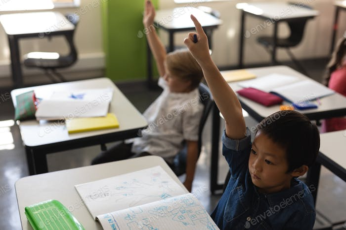High angle view of schoolboy raising hand in classroom while sitting at desk