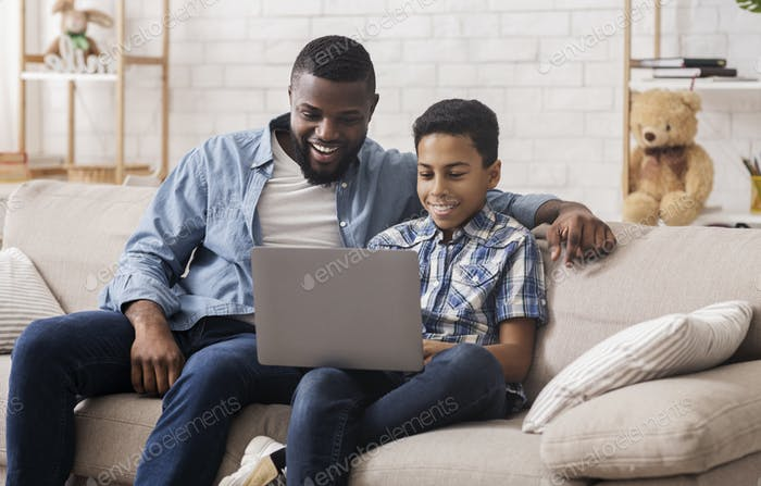 Fröhlich schwarz Sohn und Papa beobachten Comedy Film auf Laptop zusammen