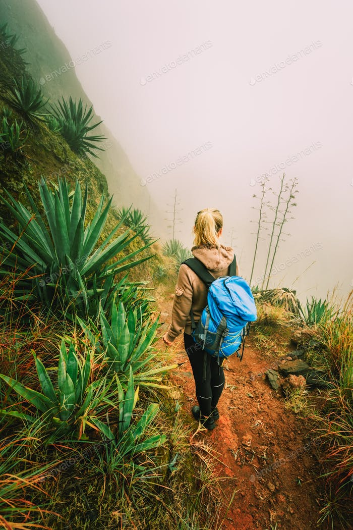 Santo Antao, Cape Verde. Women with backpack hike down the steep slope of the rock in the foggy