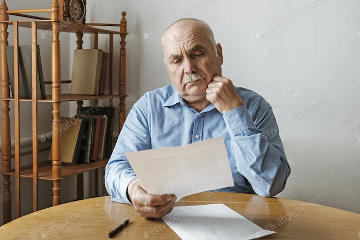 Thoughtful old man reading a paper document