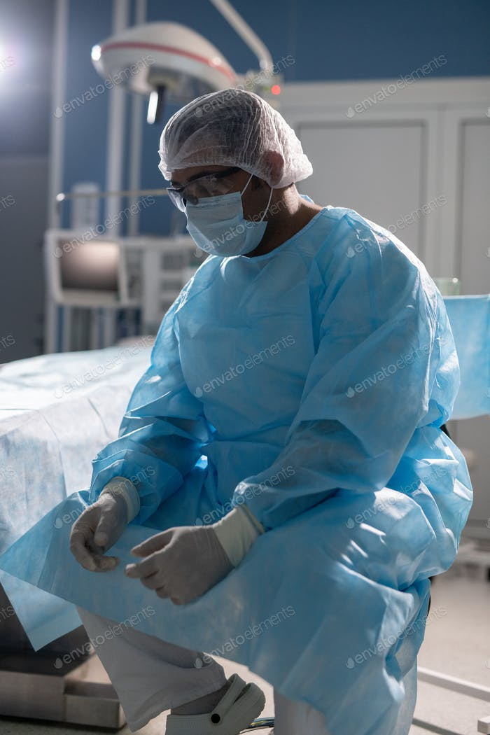 Tired surgeon in protective workwear sitting against operating table at break