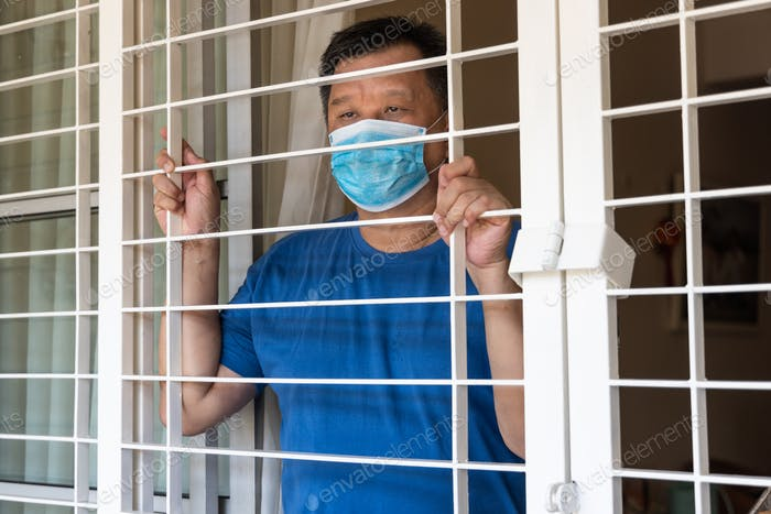 Anxious Chinese man with face mask self isolate at home for fear of covid-19 virus