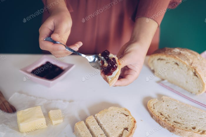 Womans hand spreads jam on homemade bread