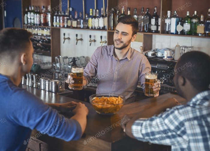 Bartender Giving Glasses With Beer To Young Guys