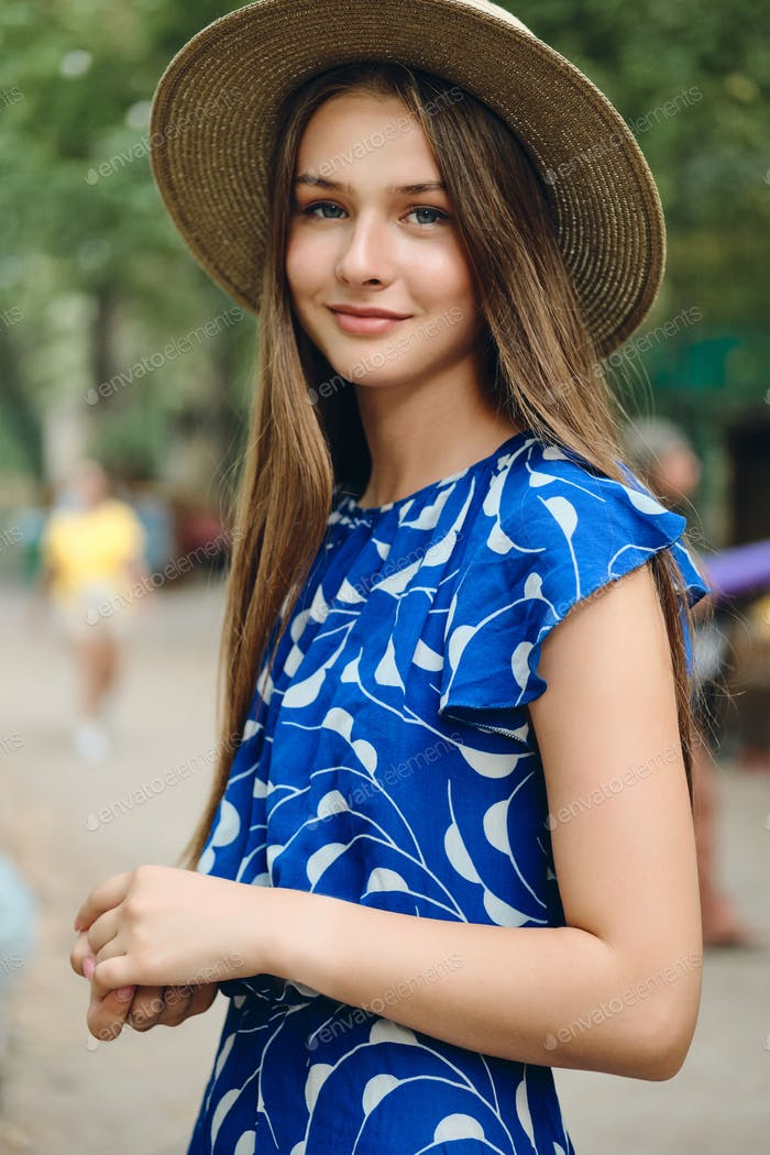 Young beautiful smiling woman in blue dress and hat dreamily looking in camera in city park