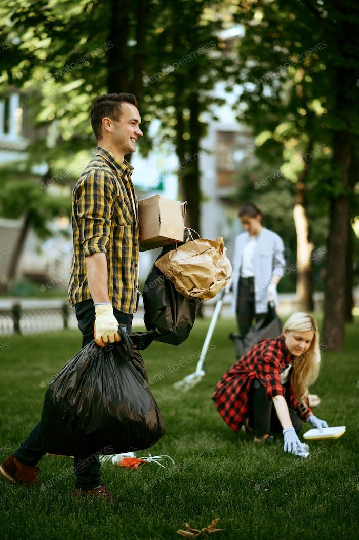 Man holds plastic trash bags in park, volunteering