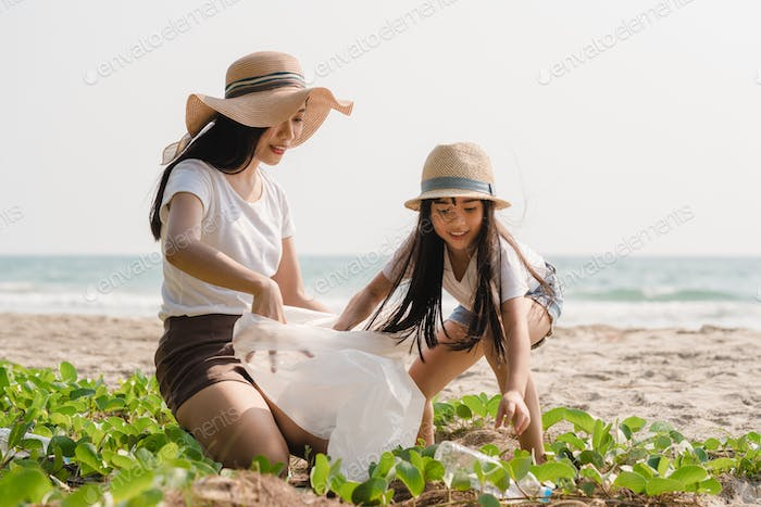 Asian young happy family activists collecting plastic waste on beach.
