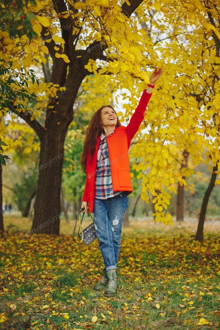 Girl with long wavy hair enjoying autumn in the park.