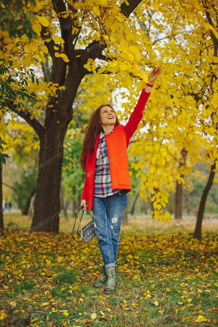 Girl with long wavy hair enjoying autumn in the park.