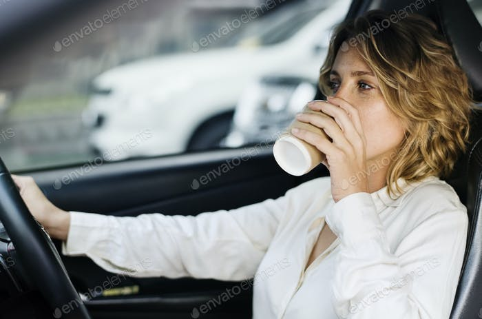Woman drinking coffee in a car