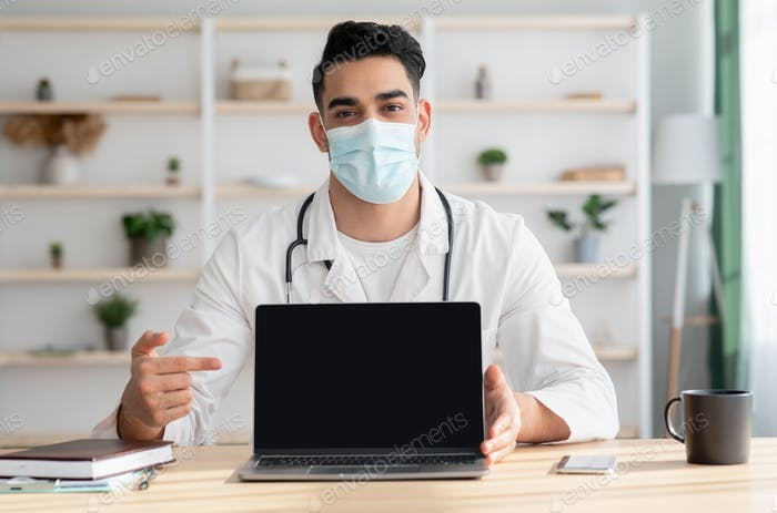 Middle-eastern man doctor in face mask pointing at laptop