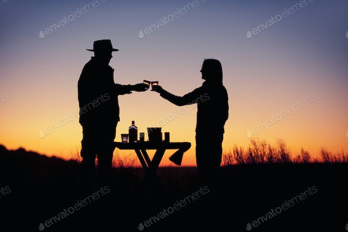 Silhouette of two people at sunset,a couple,raising glasses in a romantic toast
