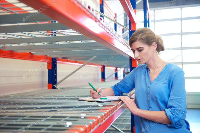 Businesswoman writing inventory on shelves in a warehouse