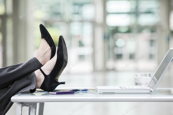 A closeup of feet and high heel shoes resting on a desk in front of a laptop computer.
