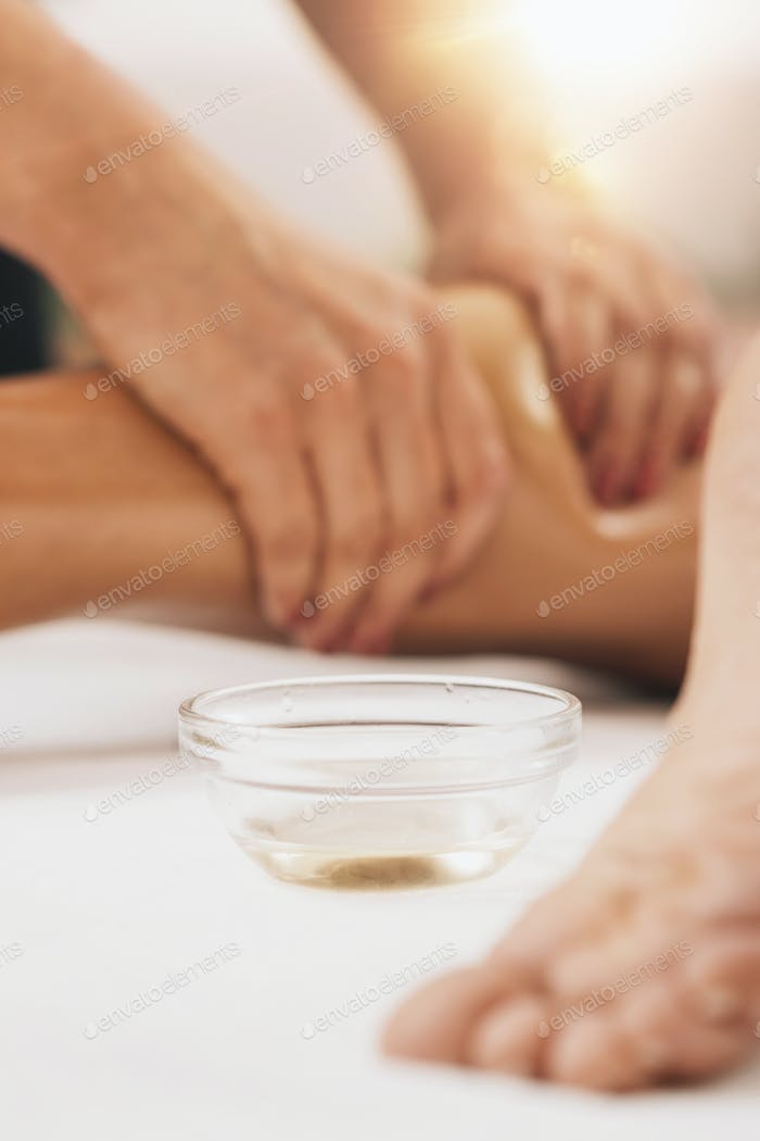 Anti cellulite leg Massage. Masseuse applying natural birch massage oil on tanned female legs