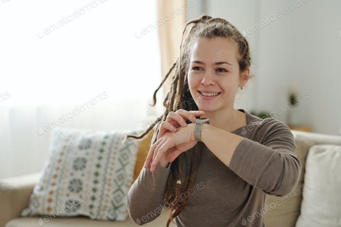 Happy girl with toothy smile keeping hand with smartwatch by her face