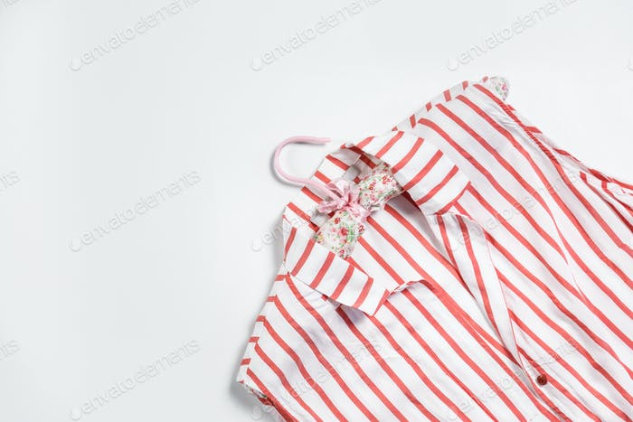 Women's striped shirt with hanger isolated on white.