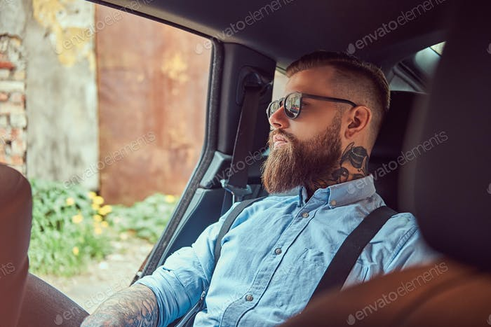 Old-fashioned tattooed hipster guy in a shirt with suspenders sitting in a luxury car on back seat.