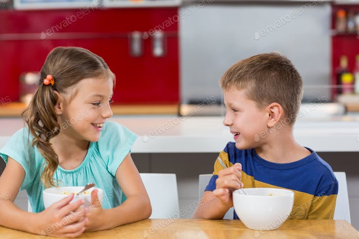 Smiling sibling having breakfast cereal in kitchen