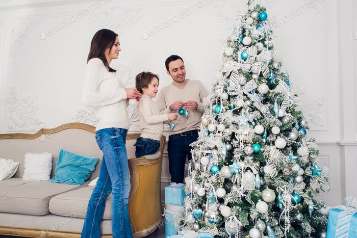 Family decorating a Christmas tree with boubles in the living-room