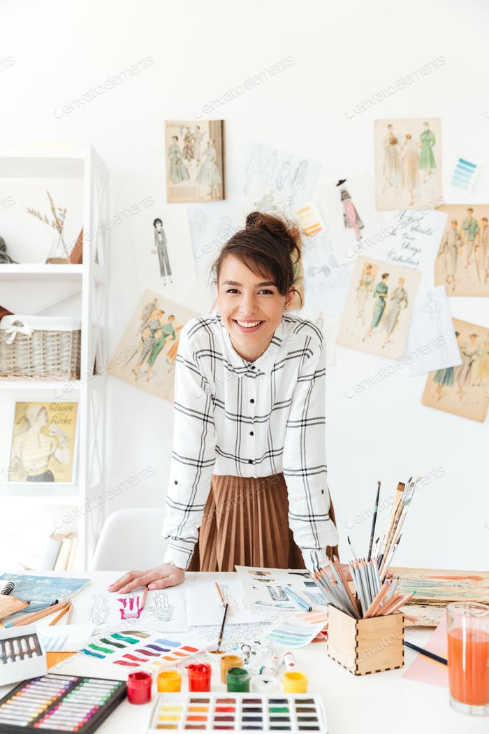 Smiling professional woman designer leaning at her work desk