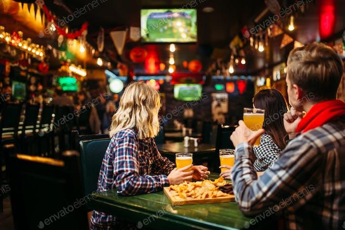 Fans beobachten Spiel und trinken Bier in der Sportbar