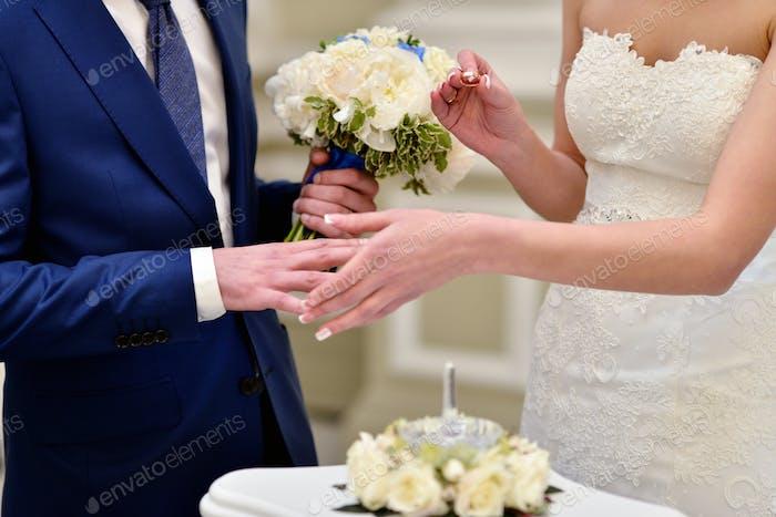 Schönheit Braut und gut aussehende Bräutigam tragen Ringe einander
