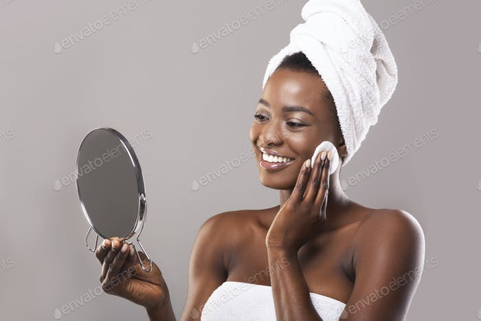 Woman looking in mirror and cleaning face with cotton pad
