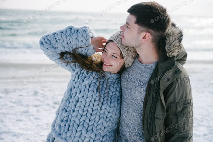Happy Young Couple Hugging on Winter Seashore