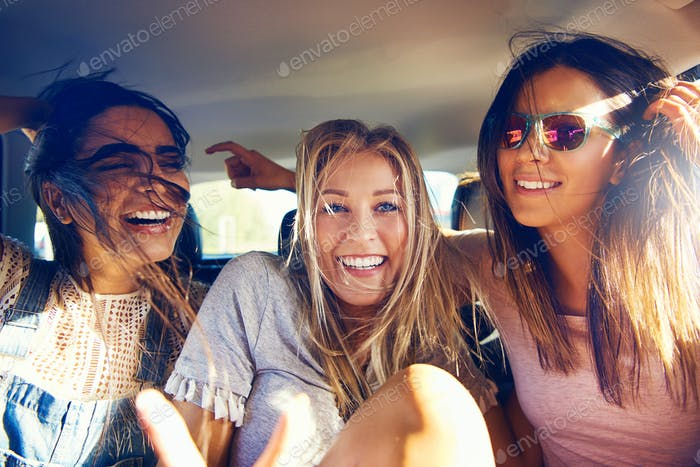 Three beautiful happy girls in a car