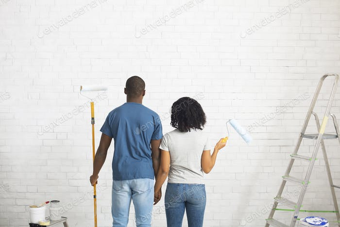 African american guy and girl with rollers in hands paint white brick wall