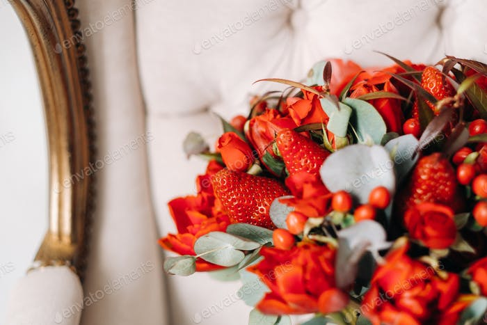 A huge bouquet of beautiful red roses with strawberries lies on the chair